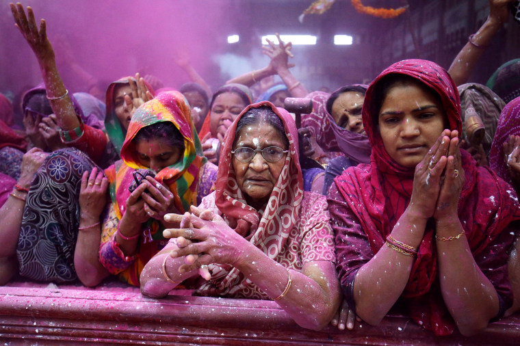 Image: Women offer prayers inside a temple during Holi celebrations in Ahmedabad