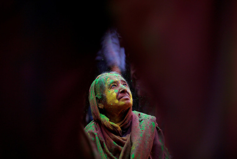 Image: A widow daubed in colours takes part in Holi celebrations in the town of Vrindavan