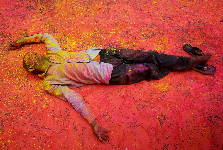 Image: A Hindu devotee, smeared in coloured powder, takes a rest on a road during a procession for Holi celebrations in Kolkata