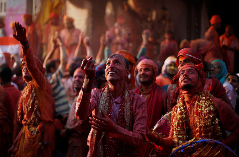 Image: Hindu devotees take part in the religious festival of Holi inside a temple in Nandgaon village