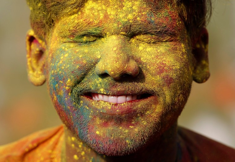 Image: A student of Rabindra Bharati University, with his face smeared in coloured powder, reacts as his fellow student throws coloured powder on his face during Holi celebrations inside the university campus in Kolkata