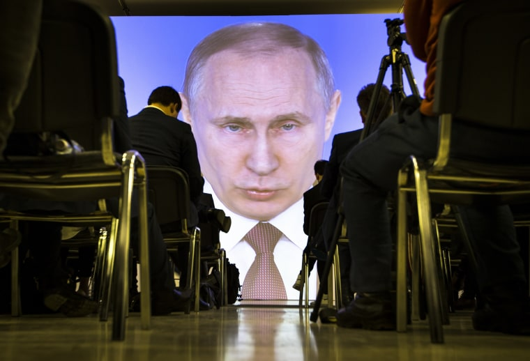 Image: Journalists watch as Russian President Vladimir Putin gives his annual state of the nation address in Moscow