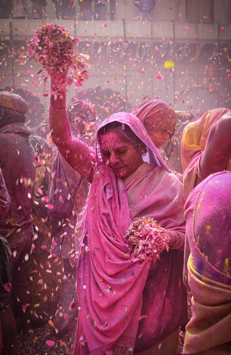 Image: An Indian widow dances covered in colored powder during Holi festival celebrations