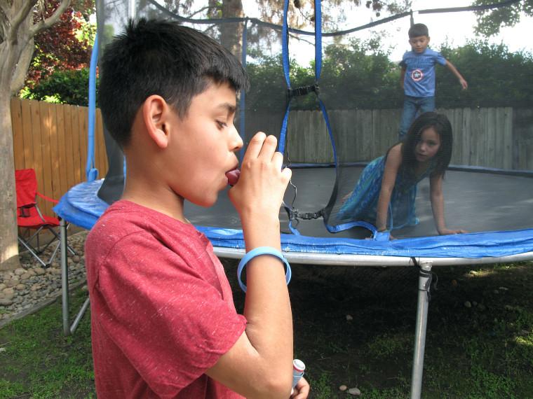 Image: Javier Sua demonstrates how he uses an inhaler