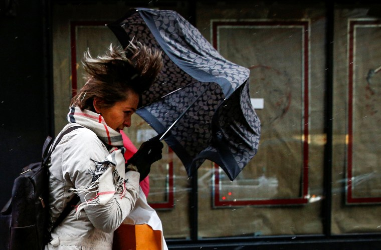 Image: People walk through Times Square during a winter nor'easter in New York