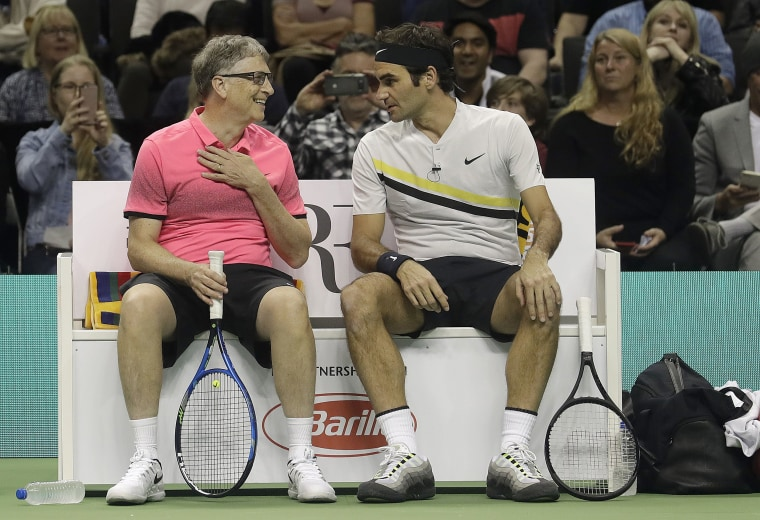 Bill Gates, left, smiles as he talks with partner Roger Federer, of Switzerland, as they play an exhibition tennis match against Jack Sock and Savannah Guthrie in San Jose, Calif., Monday, March 5, 2018.