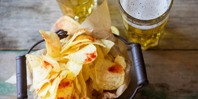 High Angle View Of Fresh Crunchy Potato Chips With Beer On Table
