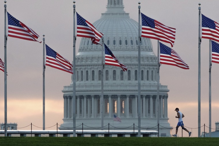 Image: An early morning runner crosses in front of the U.S. Capitol