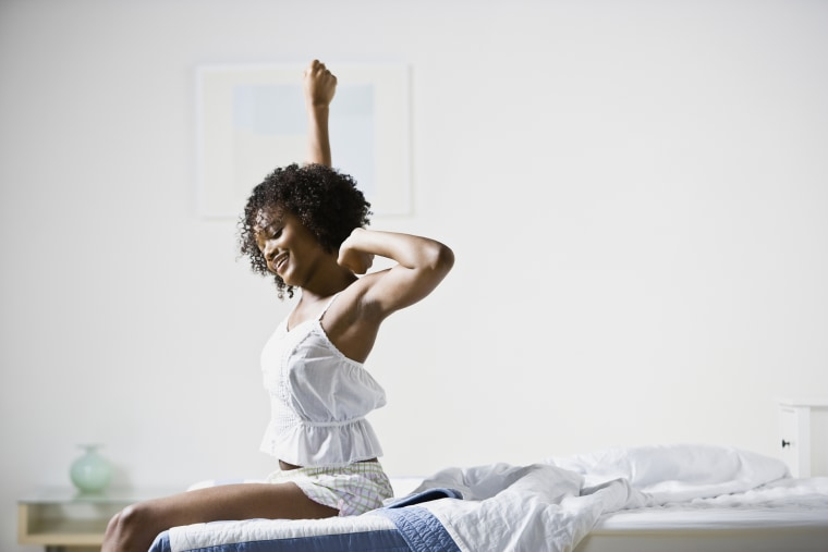 Image: A woman sitting on bed stretches