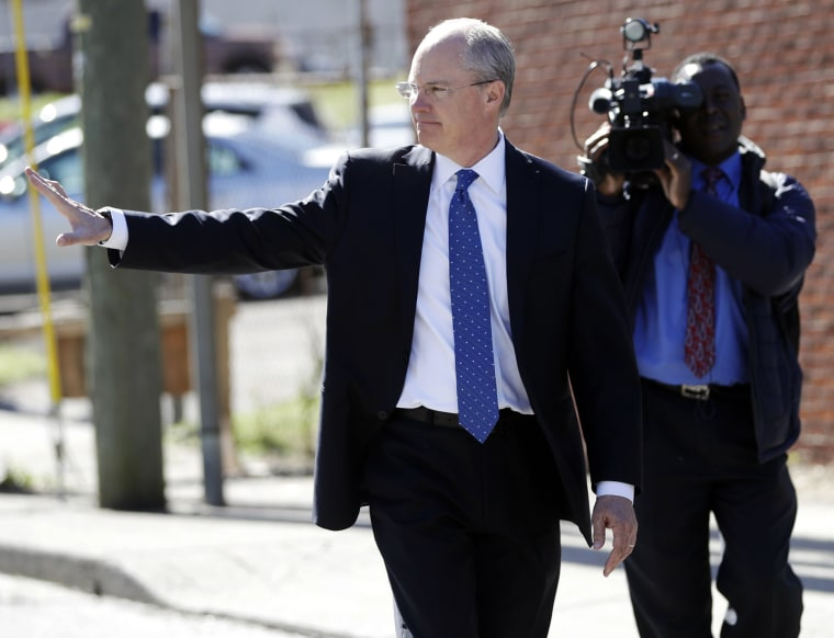 Image: Sgt. Robert Forrest waves as he walks to the Criminal Justice Annex