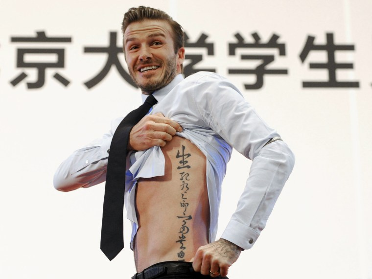 Image: David Beckham showing his tattoo after he was asked to by students at Peking University during his visit in Beijing