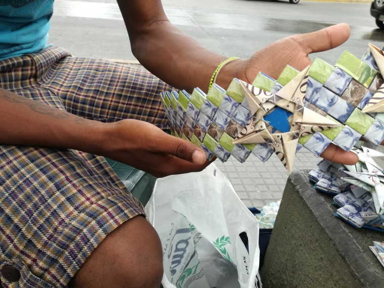 Wilmer Rojas, an artist who makes purses, wallets and baskets by folding lower denomination bills.
