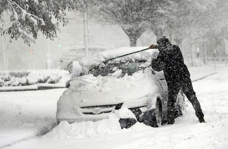 A man clears snow off of his car on State Street in Danbury on March 7.