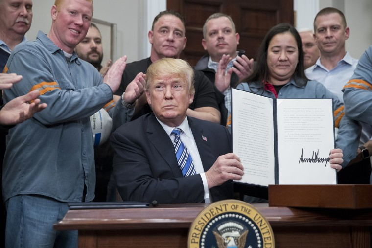 Image: President Donald Trump holds a presidential proclamation on steel tariffs