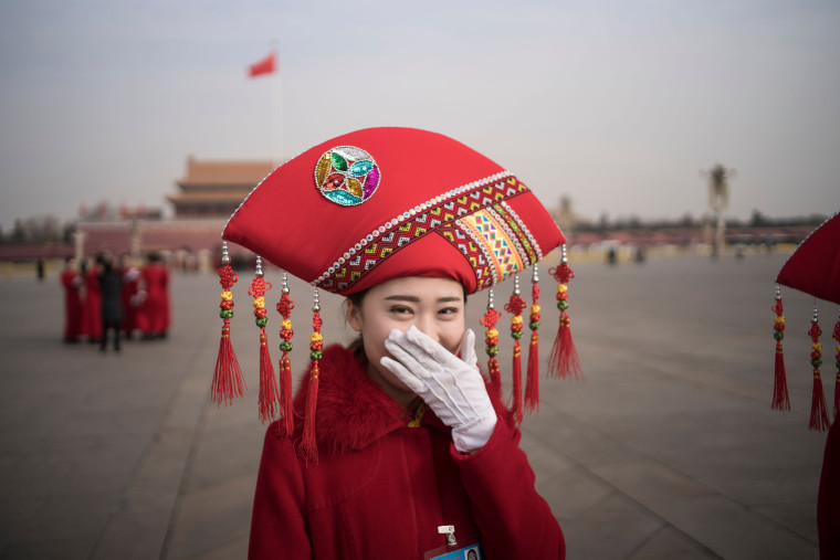 Image: A hostess smiles at Tiananmen Square during the opening session of the National People's Congress in Beijing
