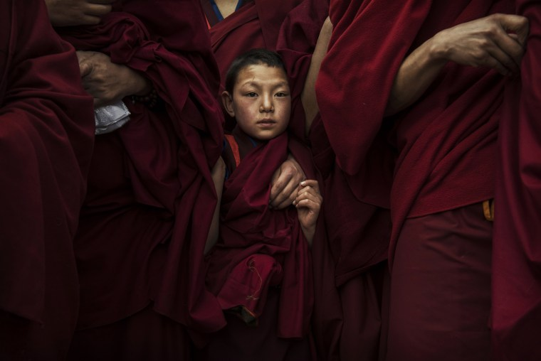 Image: A young monk waits before a Monlam procession near the Rongwo Monastery in Tongren