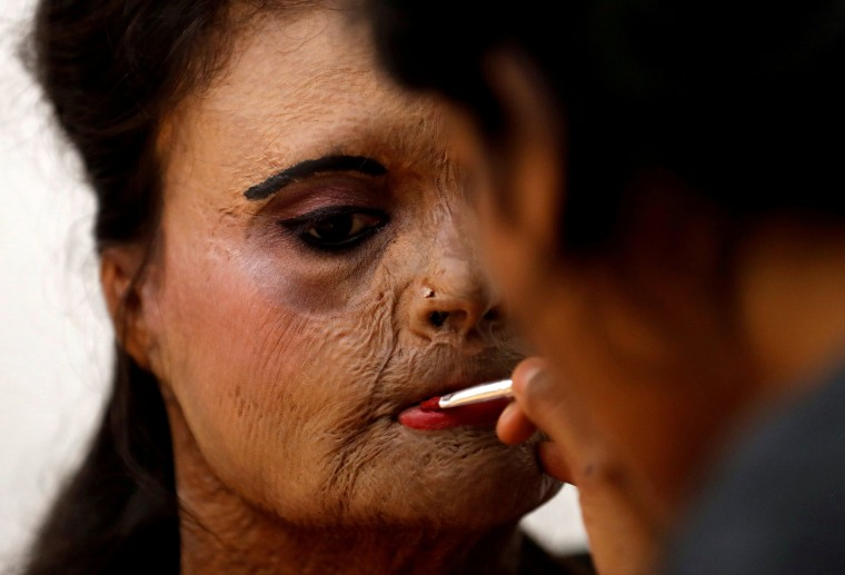 Image: An acid attack survivor has her makeup done before a fashion show to mark International Women's Day