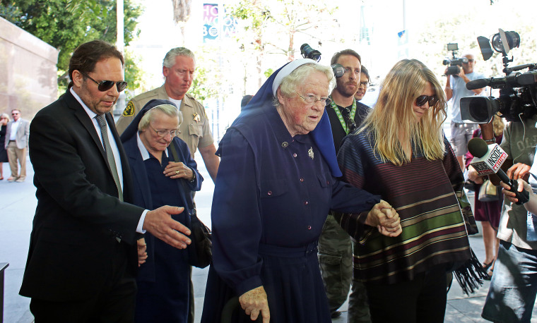 Image: Sisters Catherine Rose Holzman, second left, and Rita Callanan, center, is escorted by businesswoman Dana Hollister, right, out of Los Angeles Superior Court on Thursday, July 30, 2015.