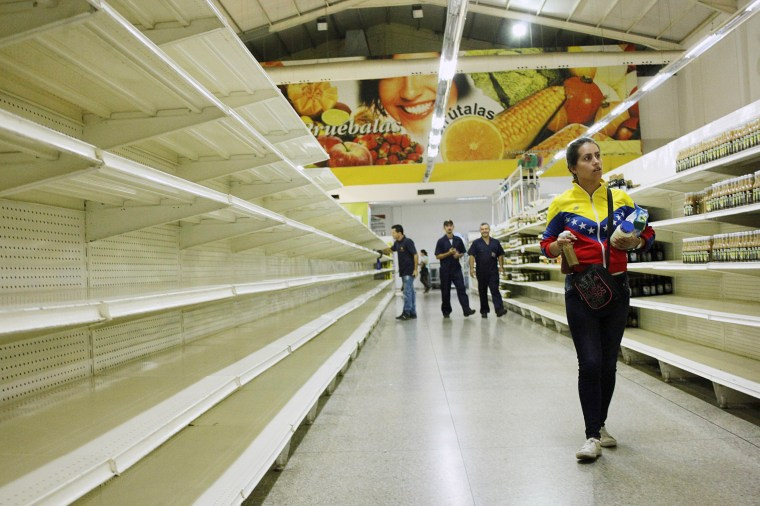 Image: A woman walks past empty shelves at a supermarket in San Cristobal, Venezuela