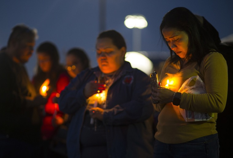 Image: Ericka Rivera, right, attends a prayer vigil
