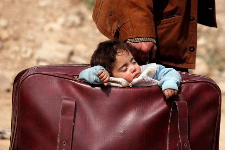 Image: A child sleeps in a bag in the village of Beit Sawa