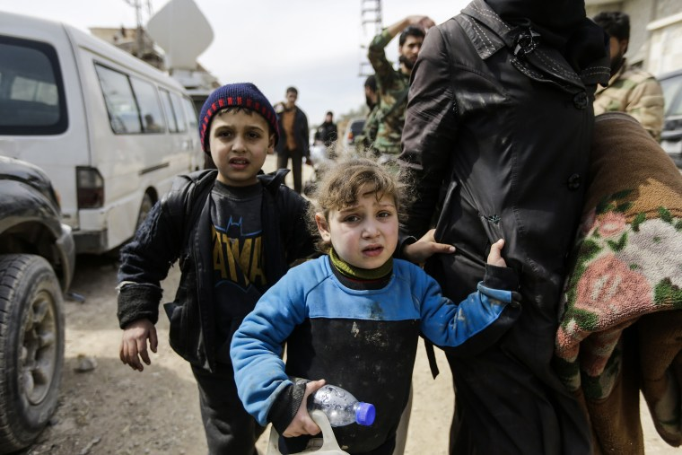 Image: A Syrian girl and boy from the Eastern Ghouta enclave walk with another woman and civilians t