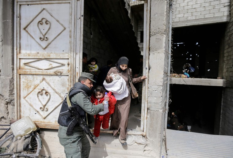 Image: A Syrian government policeman helps a child out of a building as civilians flee