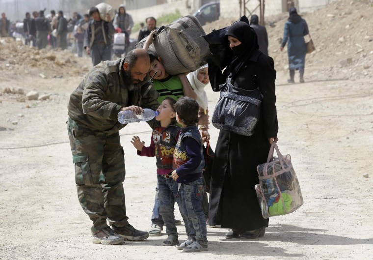Image: A member of the Syrian government forces helps children drink from a water bottle