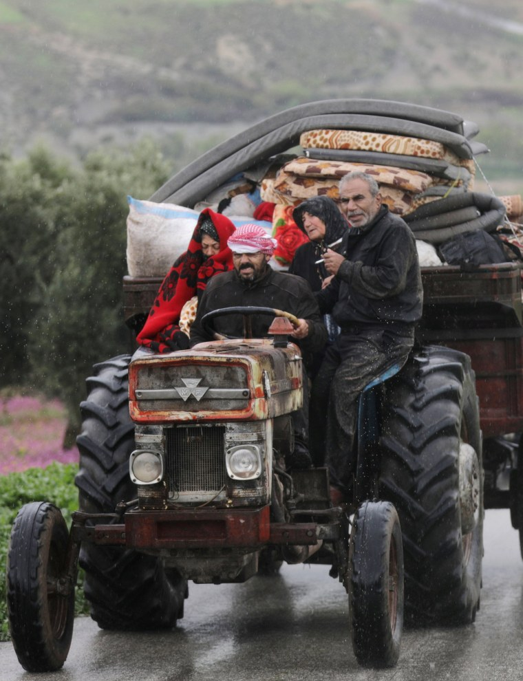 Image: People sit in a truck with their belongings in the north east of Afrin