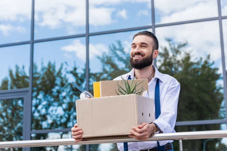 Happy Businessman With Cardboard Box With Office Supplies In Hands Standing  Outside Office Building, Quitting
