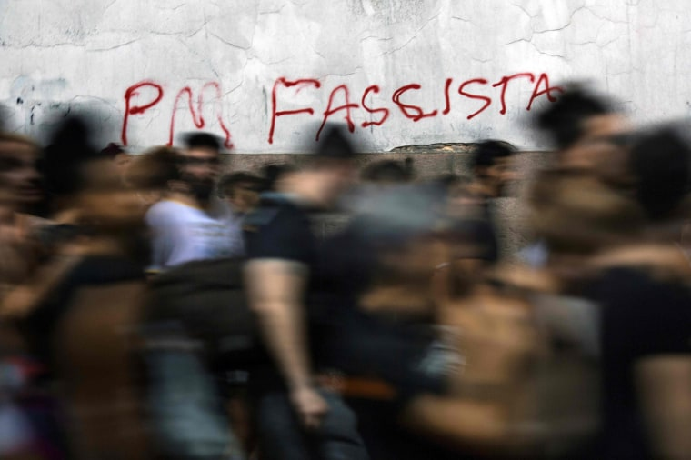 "Demonstrators walk by graffiti reading ""Fascist PM (Militarized Police)"" during a protest against the murder of councilwoman Franco. Brazilians mourned for the councilwoman and activist who was shot in the city center in an assassination-style killing on the evening prior."