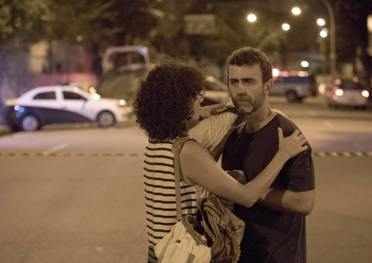 Rio's state Legislator Marcelo Freixo, right, of the same political party as the murdered council member, is comforted as he stands close to the crime scene.