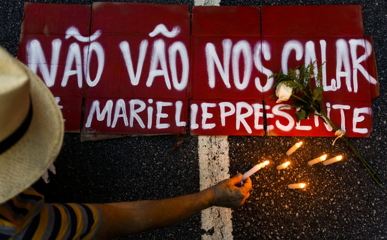 "A man lights a candle next to a sign in Sao Paulo reading ""They will not keep us quiet."""