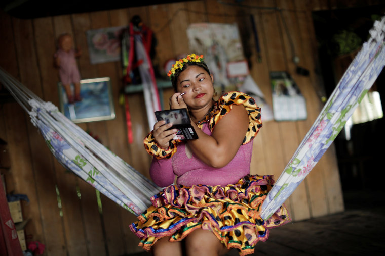 "Image: A member of the ""Bloco Bambas da Folia"" group puts on makeup"