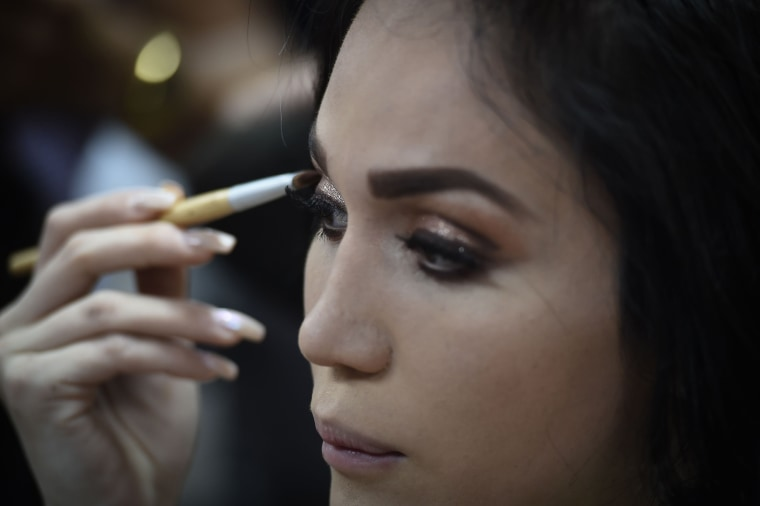 Image: Cristobal Altuzar of Mexico puts on makeup before the final round of the Miss International Queen 2018 transgender beauty pageant