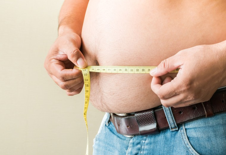 Image: Midsection Of Man Holding Measuring Tape Against Beige Background