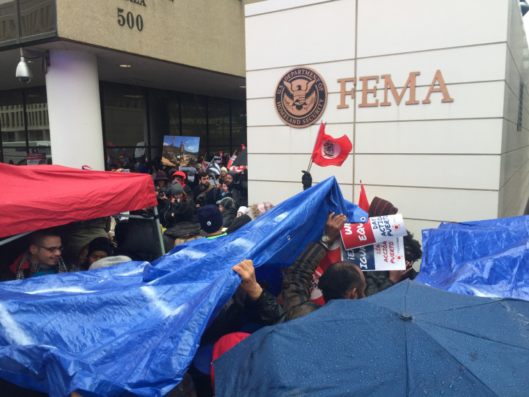 Crowds gather in front of the FEMA building in D.C. with blue tarps, symbolizing the same blue tarps that still cover homes in Puerto Rico six months after Hurricane Maria.