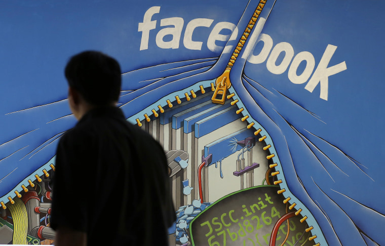 Image: A man walks past a mural in an office on the Facebook campus