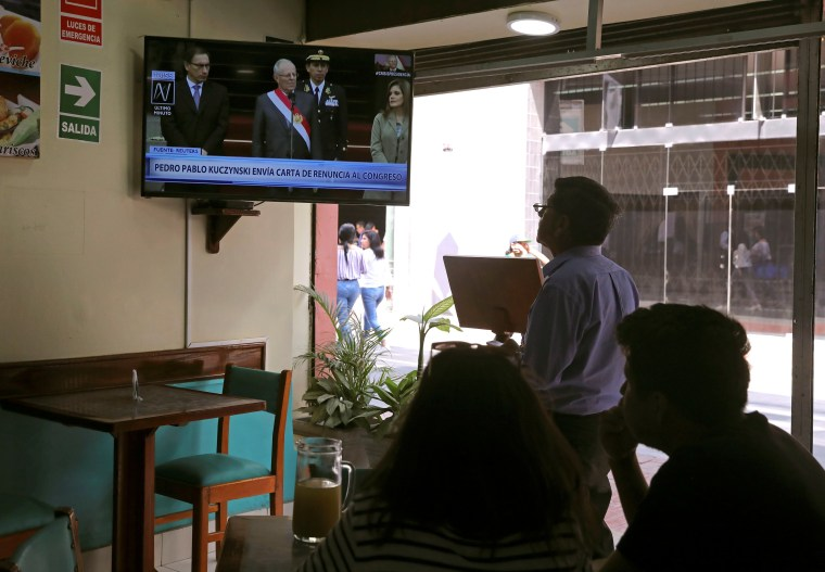 Image: People look on as Peru's President Pedro Pablo Kuczynski addresses to the nation as he resigns in Lima