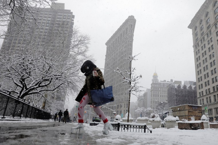 Image: A pedestrian wearing platform shoes crosses the street during a late season nor'easter in New York