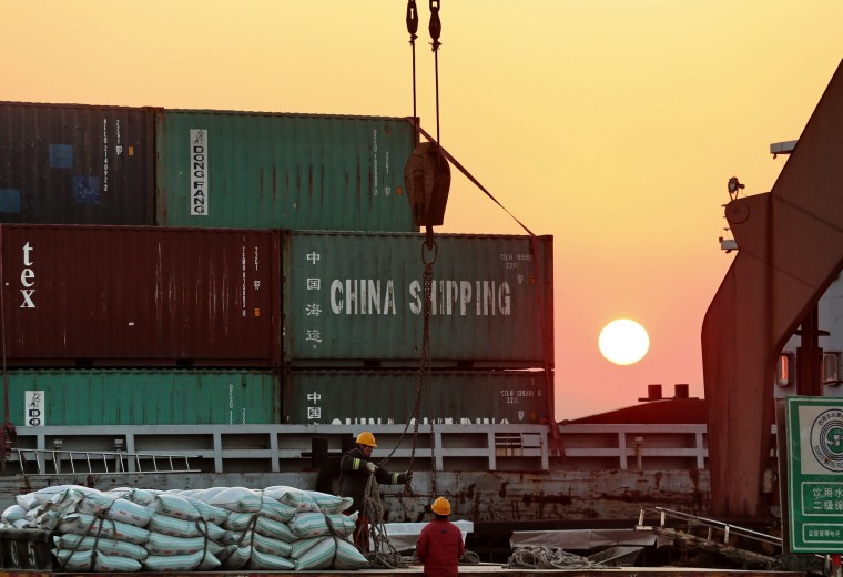Image: Workers load ships at a port in Nantong in China's eastern Jiangsu province
