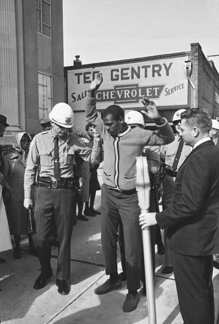 Image: Police frisk one of six African Americans arrested as they tried to get in the voter registration line in Selma