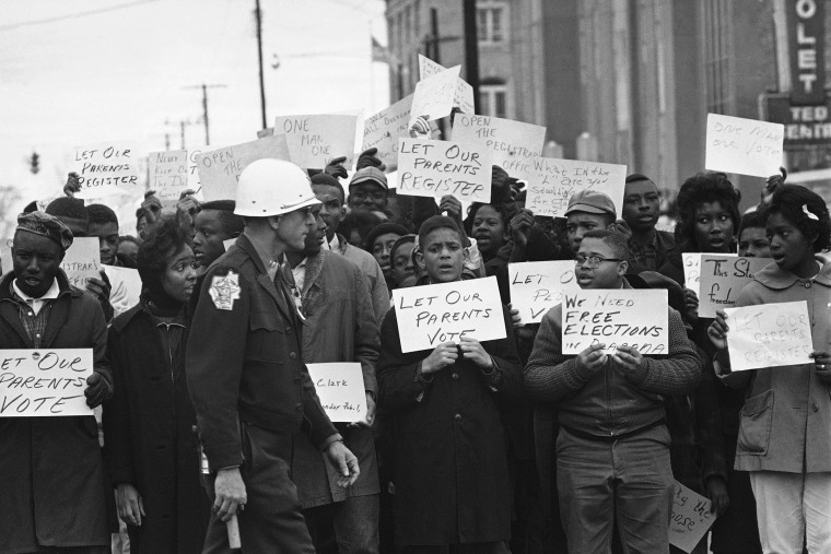 Image: Sign-carrying young African Americans sing and chant as they stage a demonstration at the courthouse