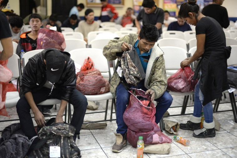 Image: A group of deported immigrants gather their belongings