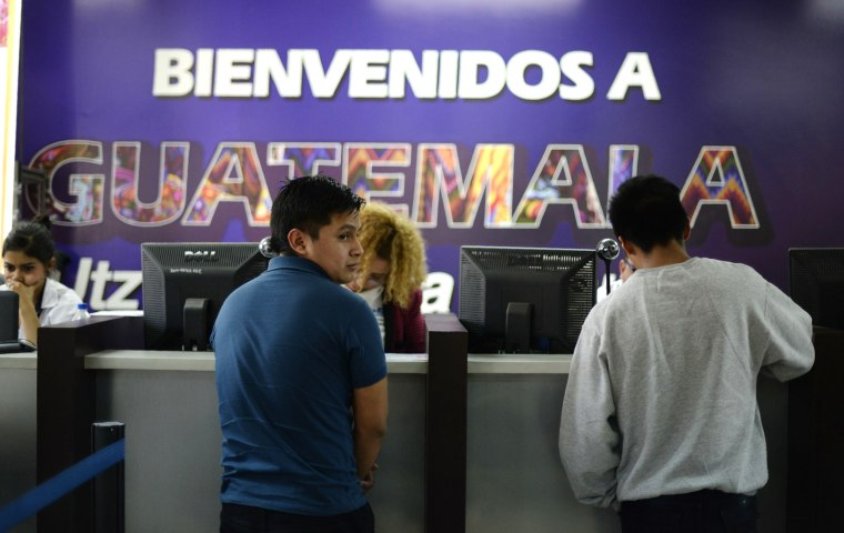 Image: Deported immigrants wait to be registered