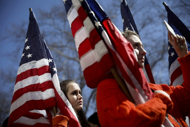 High school students from New Jersey hold American flags as they attend the March For Our Lives just north of Columbus Circle, in New York City on March 24, 2018. More than 800 related events are taking place around the world to call for legislative action to address school safety and gun violence.