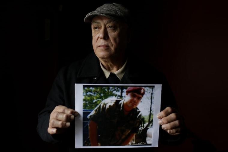 Image: Miguel Perez with a photo of Miguel Perez Jr.