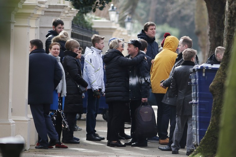 Image: People hug as they carry luggage leaving the Russian Embassy in London