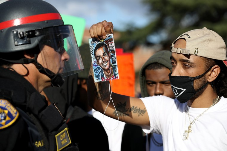 Image: A Black Lives Matter protester holds a photo of Stephon Clark in front of a California Highway Patrol officer