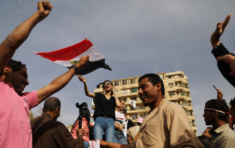 Image: A woman waves an Egyptian flag during the presidential election in Cairo